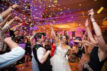 Bride & Groom laughing with colourful confetti thrown into the air